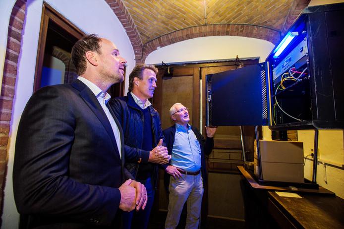 Lokale omroep VLHO is terug in de toren. Burgemeester Ryan Palmen (l) en VLOH-voorzitter Hans van der Wiel schakelden maandagavond samen met Kees Michels (r) de zendapparatuur weer aan.
