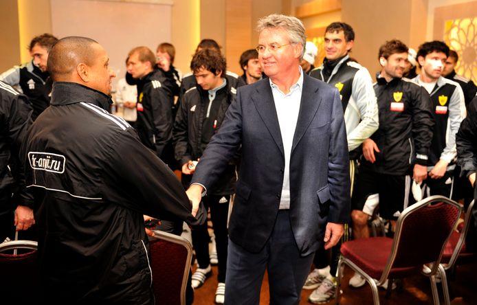 Guus Hiddink schudt de hand van de legendarische verdediger Roberto Carlos. Guus startte in 2012 bij de Russische club  Anzhi Makhachkala. Hiddink ging daar een exorbitant hoog salaris verdienen.