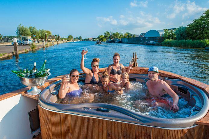 Mariel Dijkstra (met zonnebril en bikinitopje) van PUHA neemt met haar vriendinnen en echtgenoot een bad in haar eigen jacuzzisloep.