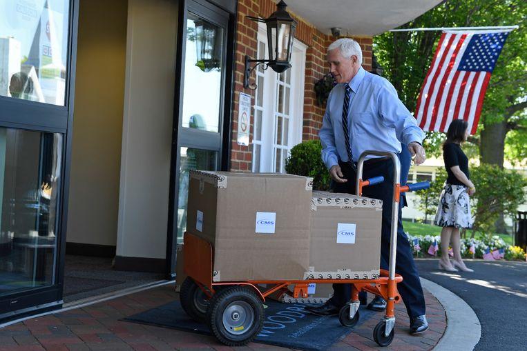 Mike Pence levert dozen vol beschermingsmateriaal af bij een ziekenhuis in Virginia. Beeld AP