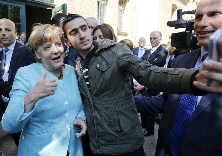 Angela Merkel gaat op de foto met een migrant, in 2015 - de tijd van 'Wir schaffen das'.  Beeld reuters