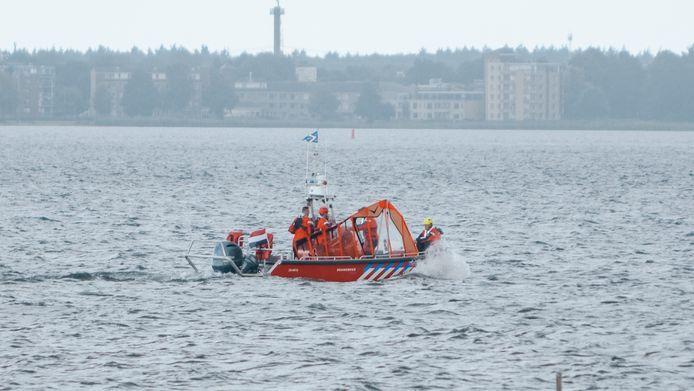 De windsurfer werd uit het water gehaald door de brandweer.