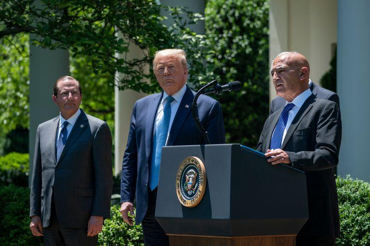 Moncef Slaoui, in mei aangesteld als hoofd van 'Operatie Warp Speed', doet in de rozentuin van het Witte Huis zijn vaccinbeleid uit de doeken. President Trump hoort dat het goed is. Beeld Getty Images