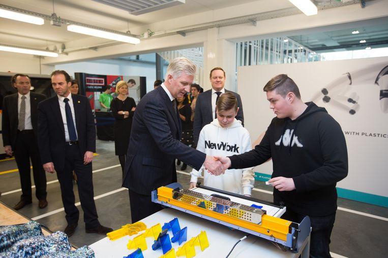 Mil en Rens, leerlingen aan het technisch instituut Sint-Michiel uit Bree, tonen de koning hoe ze van gerecyleerd plastic allerlei gebruiksvoorwerpen maken.