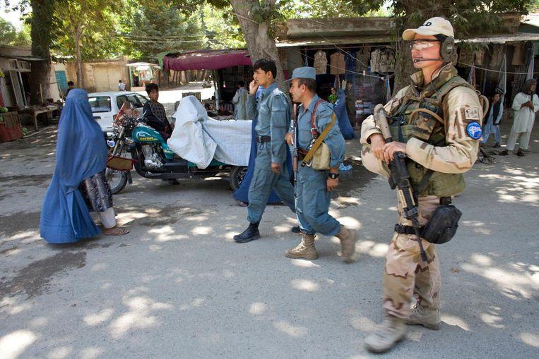 Nederlandse militairen begeleiden in 2018 Afghaanse politieagenten tijdens een patrouille in Khanabad. Beeld Ton Koene