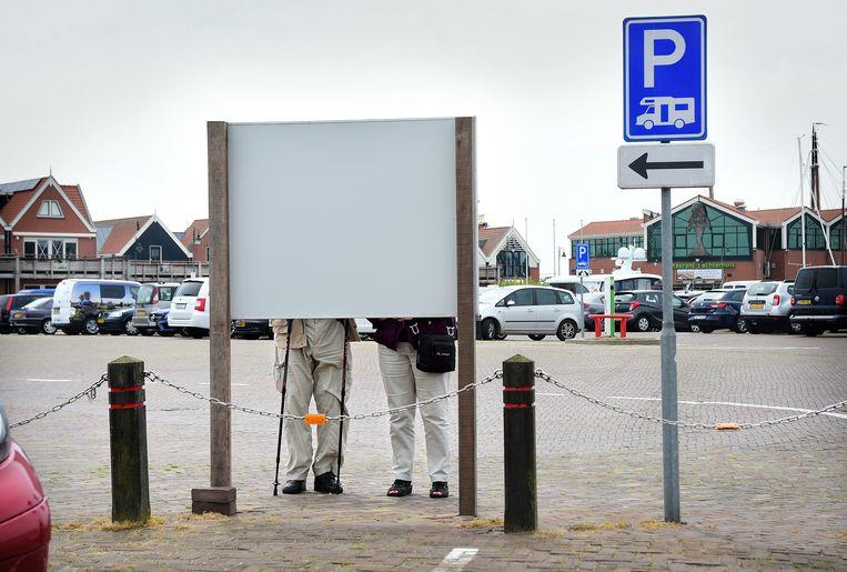 kGepensioneerd echtpaar bekijkt een bord met toeristische informatie in Urk. Beeld Marcel van den Bergh