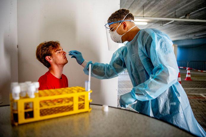 Een medewerker van de GGD neemt een coronatest af.
