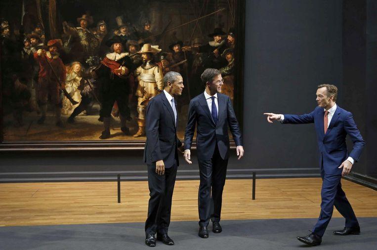 Wim Pijbes geeft Barack Obama (L) en Mark Rutte (R) aanwijzingen terwijl ze zich voorbereiden om te poseren voor de Nachtwacht, in maart 2014. Beeld EPA
