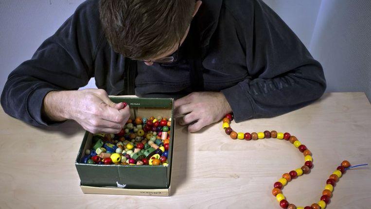 Een autistische man maakt een kralenketting. Beeld AFP