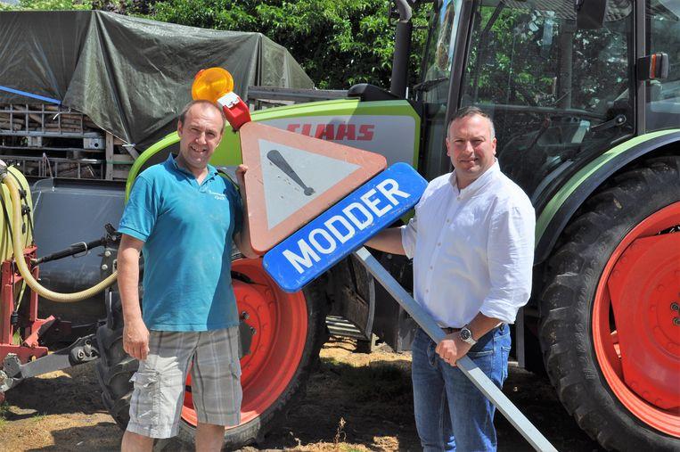 Landbouwer Luc Basteleus kreeg van milieuschepen Gunther Coppens (N-VA) het eerste verkeersbord overhandigd in Sint-Pieters-Leeuw. Landbouwers kunnen voortaan zelf modder op de weg signaleren.
