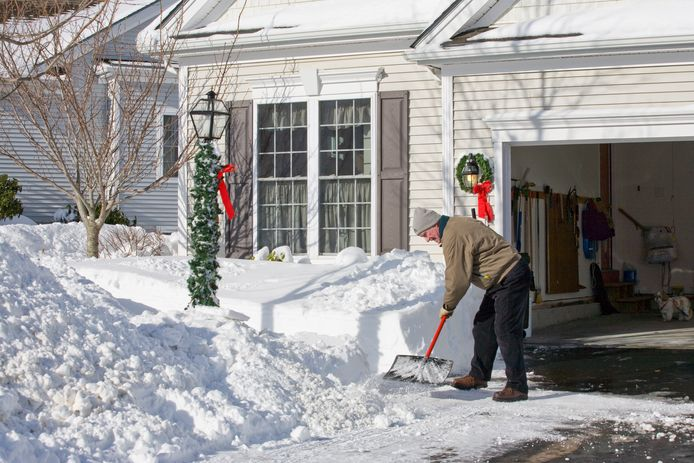 Senior man shoveling after a fresh snow storm at Christmas
