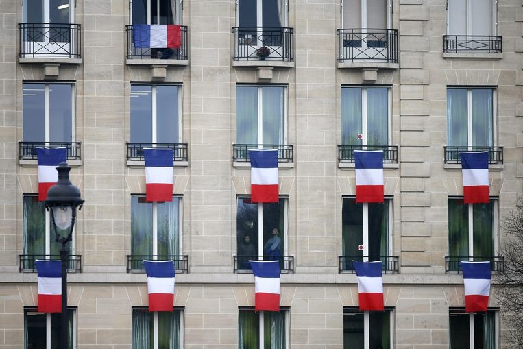 Fransen hangen hun vlaggen uit tijdens de nationale herdenking van de aanslag van 13 november. Beeld AFP