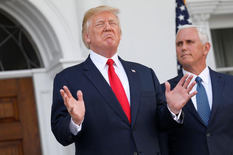 Donald Trump spreekt met journalisten in Trumps golfrestort in Bedminster, New Jersey. Vicepresident Mike Pence staat aan zijn zijde. Beeld REUTERS