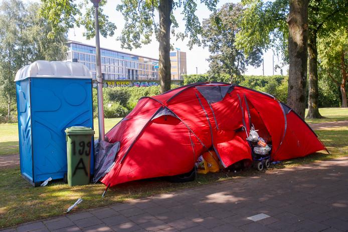 Het bankje (verstopt onder de tent) waarop de dakloze vrouw ruim twee weken bivakkeerde. Woensdag is ze vertrokken.
