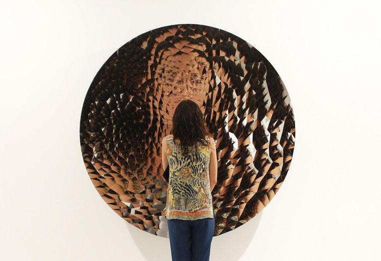Een vrouw gereflecteerd in een naamloos kunstwerk van Anish Kapoor. Beeld Reuters