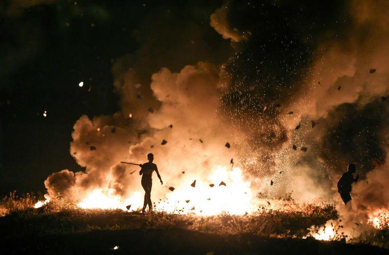 Palestijnse betogers steken autobanden in brand tijdens een demonstratie aan de Gazastrook. Beeld AFP