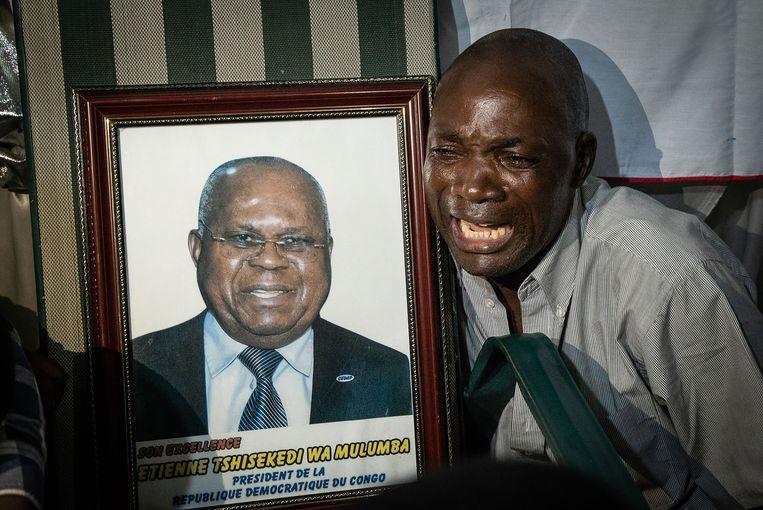 Een aanhanger van Felix Tshisekedi huilt van blijdschap nadat de uitslag van de Congolese verkiezingen bekend is gemaakt. Naast hem een portret van Etienne Tshisekedi, de vader van Felix.   Beeld AFP