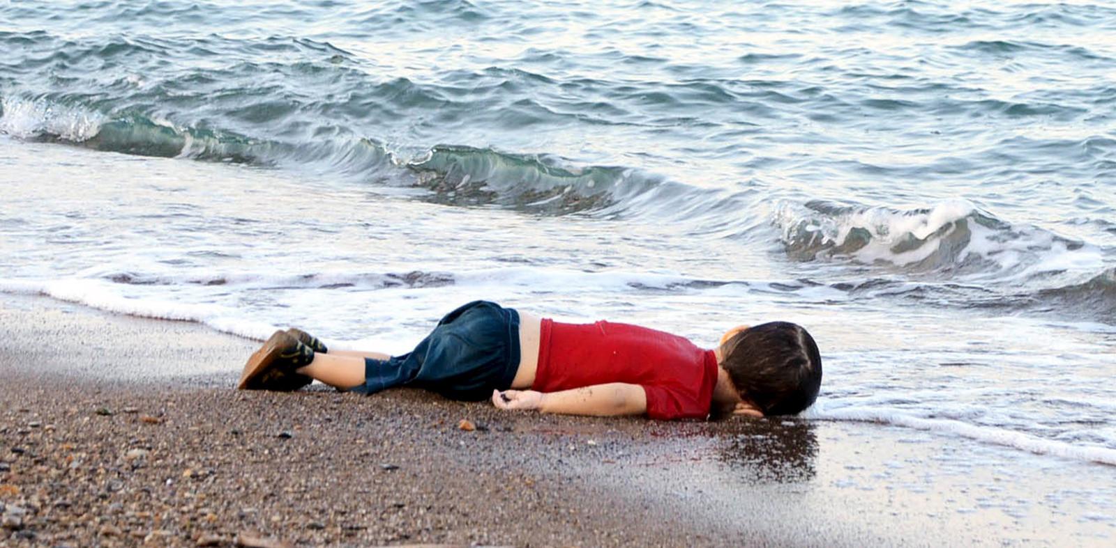 """Dans les heures qui ont suivi le double naufrage, une série de photos d'une des victimes, un bambin âgé de quelques années à peine, a envahi les réseaux sociaux sous le mot-dièse #KiyiyaVuranInsanlik (""""l'humanité échouée"""" en turc)."""