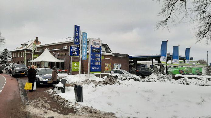 Een winters beeld van supermarkt, carwash en tankstation Derks in Overasselt.