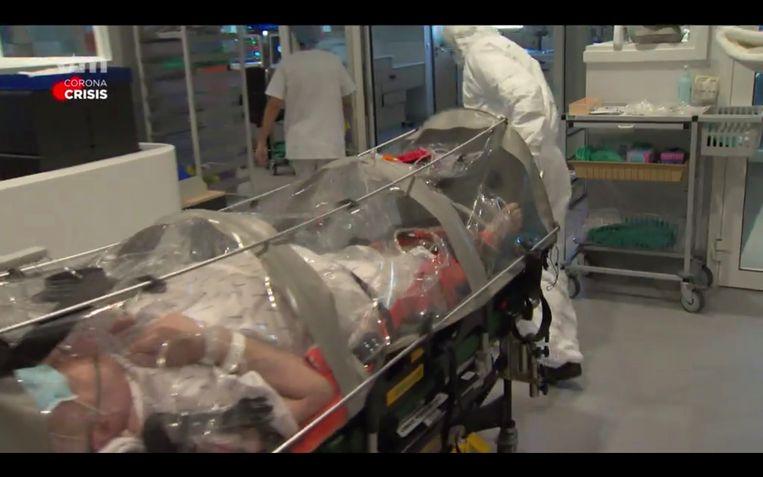Coronapatiënten worden in het Luikse CHC-ziekenhuis vervoerd in hermetisch afgesloten plastic kokers. Beeld VTM nieuws
