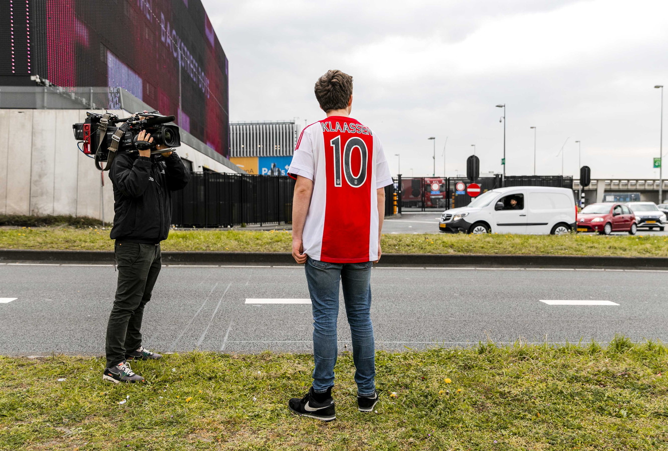 Een fan wacht de spelersbus van Ajax op bij de Johan Cruijff Arena.
