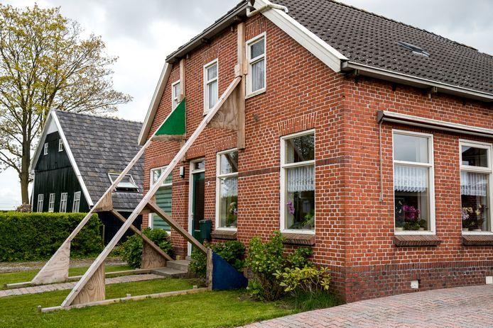Een beschadigde woning wordt versterkt door stutten in aardbevingsgebied Loppersum.