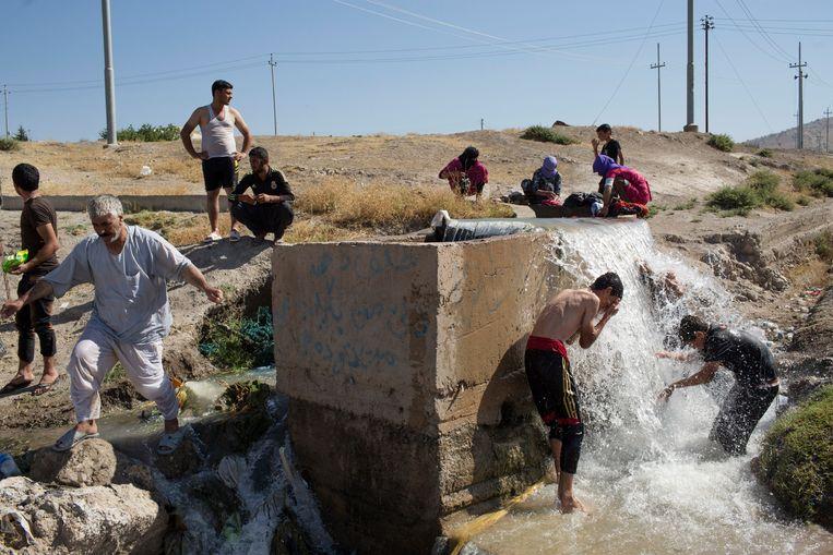 Vluchtelingen baden langs de weg in Dayrabun, Irak. 'We voelen ons tweederangsburgers.' Beeld NYT