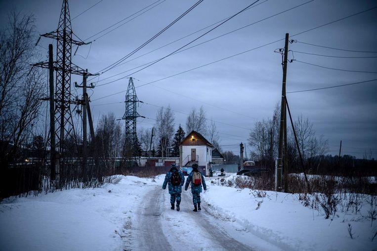Twee bewakers van de Russische federale gevangenisdienst lopen richting de ingang van strafkolonie N2 in Pokrov, waar oppositieleider Aleksej Navalny een straf van 2,5 jaar uitzit. Beeld AFP