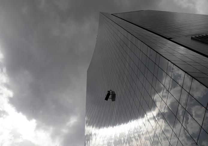 In Mexico-City wast een glazenwasser de ramen terwijl de dreigende lucht boven hem een regenbui aankondigt. Foto Henry Romero