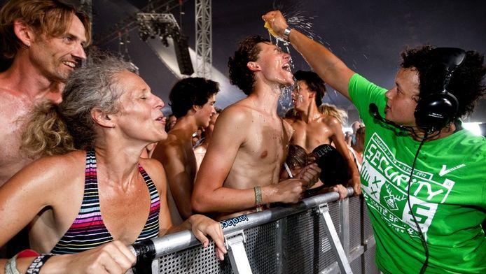 Festivalbezoekers krijgen een spons met water over zich uitgeknepen (niet tijdens Decibel)