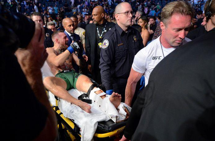 Conor McGregor wordt per brancard afgevoerd nadat hij zijn been heeft gebroken in het gevecht met Dustin Poirier.
