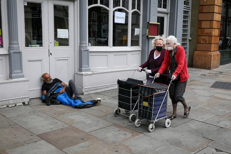 Vrouwen met winkelcaddy's lopen voorbij een dakloze man in Londen. Beeld REUTERS