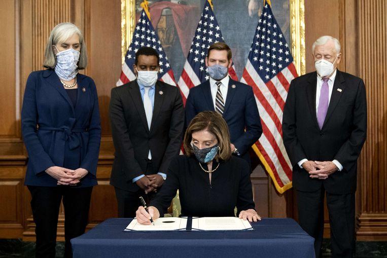13 januari, Nancy Pelosi, de Democratische voorzitter van het Huis van Afgevaardigden, ondertekent het besluit van het Huis tot impeachment van Donald Trump. Beeld AFP