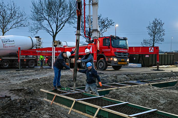 De vloer wordt gestort voor de Vakopleiding Metaal met de witte helmen op Martien Kats (l) en Kees Timmermans van SVM.
