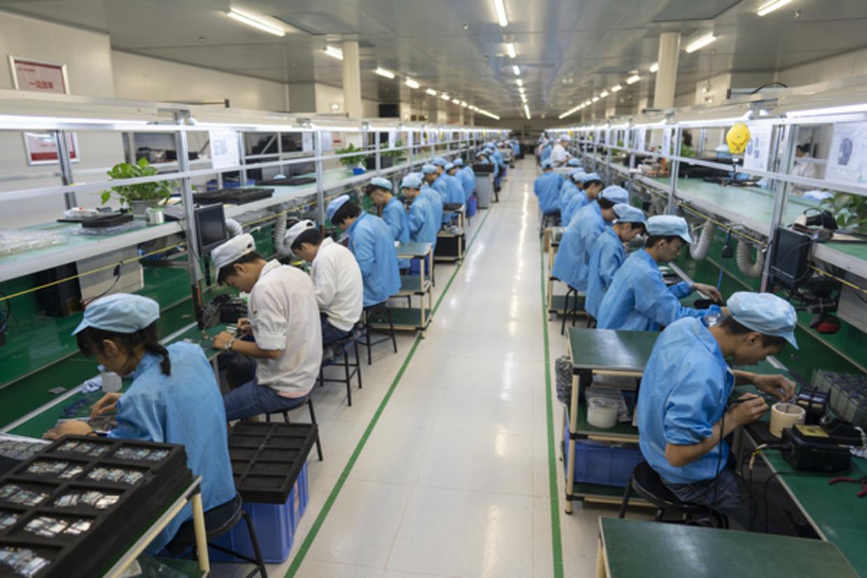 Productielijn voor consumentenelektronica bij Koomi Intelligent Technology in Shenzhenmi. Beeld Theodore Kaye