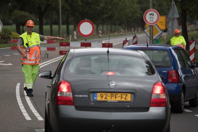 Een verkeersregelaar maakt weggebruikers op de kruising Nijverdalseweg-parallelweg duidelijk dat ze de weg af moeten.