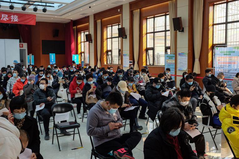 Mensen wachtenj om te worden ingeënt tegen COVID-19 in een vaccinatiecentrum in Peking, China, 27 februari 2021.  Beeld EPA