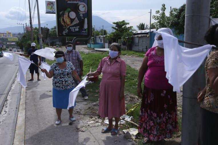 Vrouwen in El Salvador zwaaien langs de weg met witte vlaggen als een noodkreet voor voedsel Beeld REUTERS