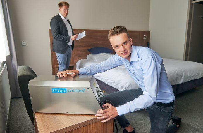 Boy Baaijens installeert een apparaat dat de lucht zuivert bij City Hotel te Oss. Op de achtergrond Gijs van Kaathoven, manager van het Hotel .