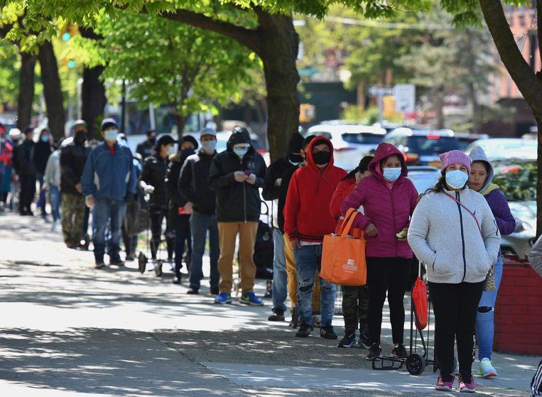 Amerikanen staan in Brooklyn, New York in de rij voor voedselhulp.  Beeld AFP