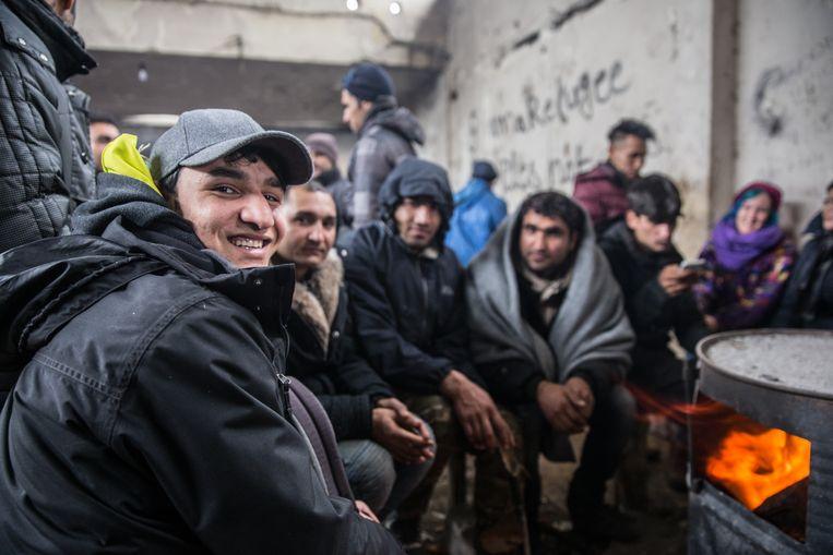 Scholier Rezwan Ullah (petje) tussen Afghaanse landgenoten die soms al jaren in een fabrieksruïne 'wonen' aan de rand van het Servische stadje Šid, vlakbij de Kroatische grens.  Beeld Yassine Atari