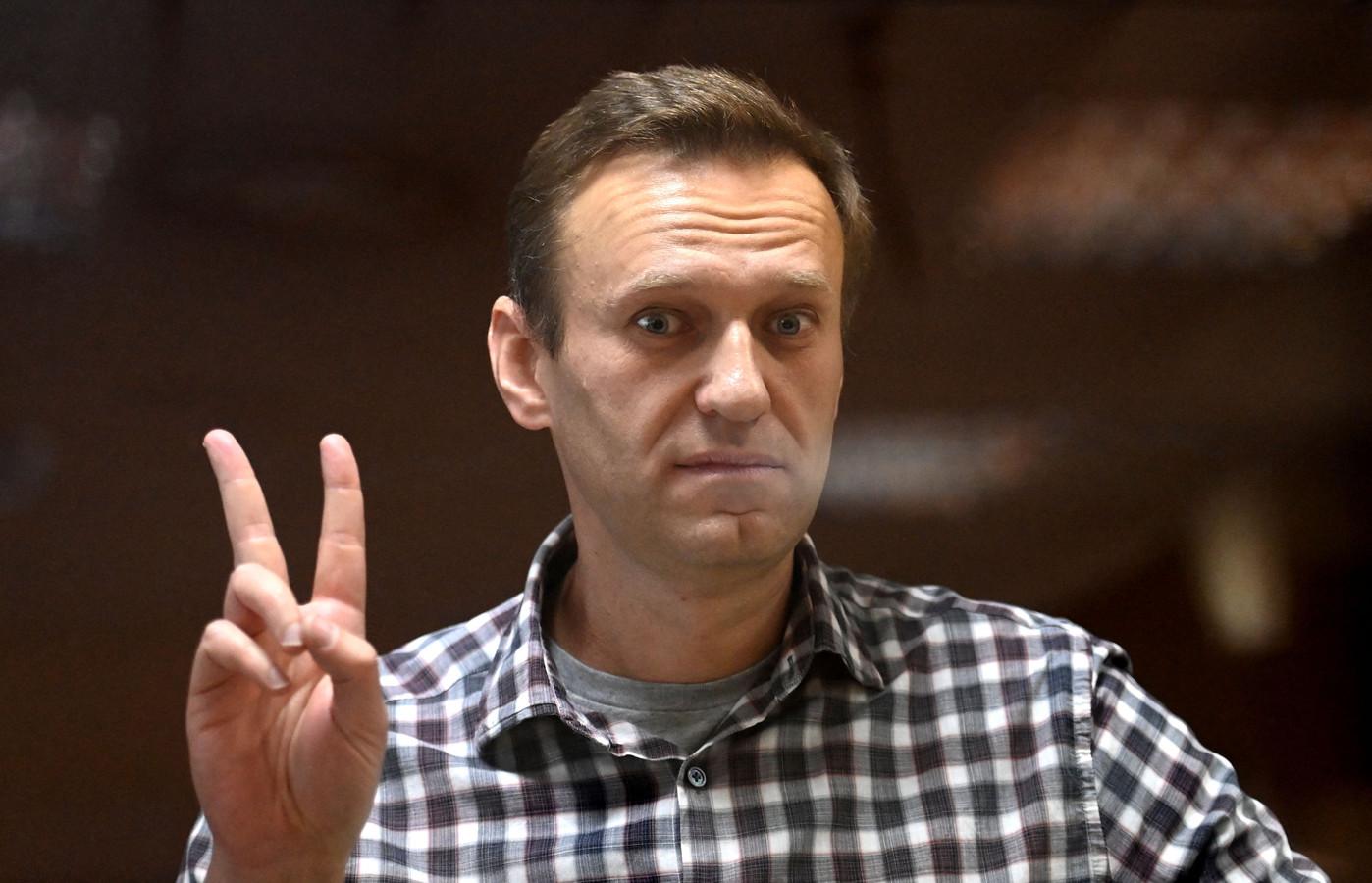 Oppositievoerder Navalny maakt het vrijheidsteken in de rechtszaal in Moskou.