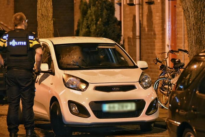 Politie doet onderzoek bij een geparkeerde auto die geraakt werd door een kogel.