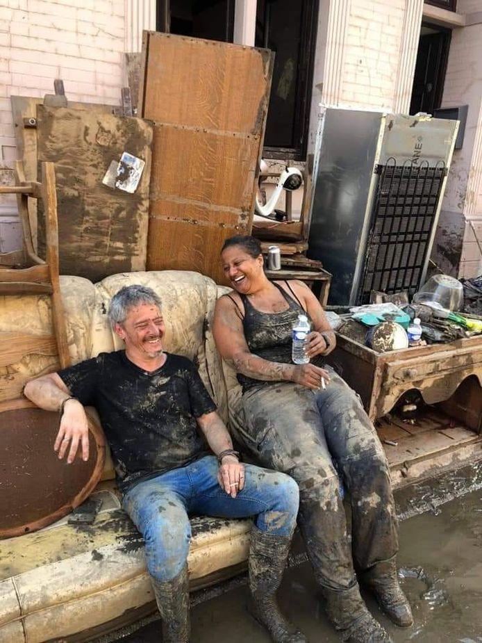 Vrijwilligers Frederic en Ysabelle lachend op een nog besmeurde zetel voor een leeggehaald huis in Chênée