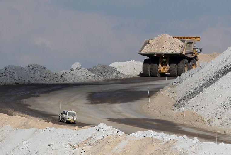 Een auto volgt een enorme mijntruck op weg naar de top van een steenkolenmijn bij Gunnedah, Australië. Beeld null