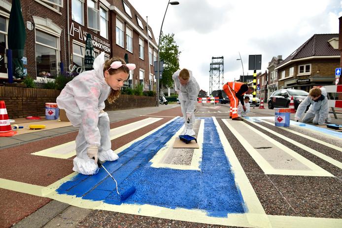 Leerlingen van de Theo Thijssenschool in Waddinxveen beschilderen een zebrapad. Op de voorgrond staat initiatiefneemster Mouna (7).