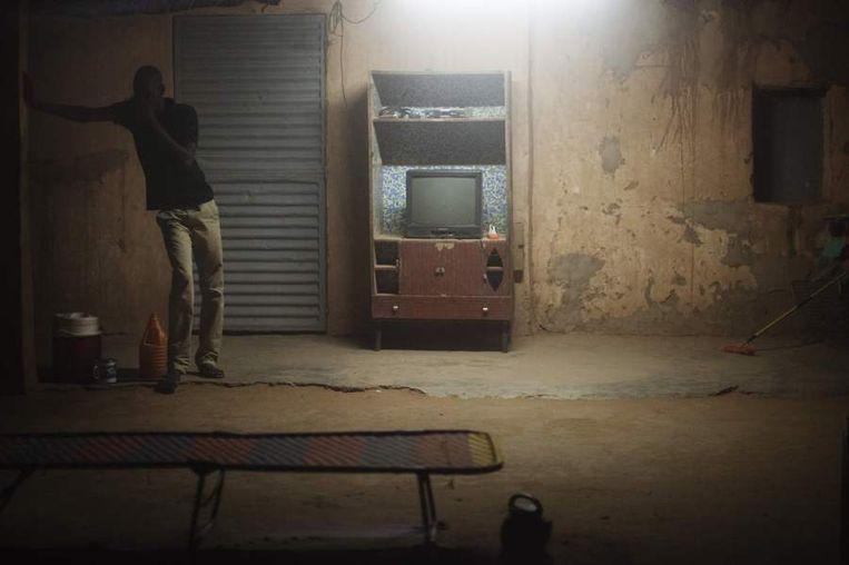 Een man bedekt zijn gezicht tijdens een nachtelijke zandstorm bij een hotel in Arlit. <br /><br />De stad Arlit in Niger is nog niet veel beter geworden van de lucratieve mijnenindustrie daar. Arlit werd in 1969 opgericht na de vondst van uranium, waarna Frankrijk er de mijnenindustrie ontwikkelde. Nu zijn er twee grote uraniummijnen, in Arlit - waar inmiddels zo'n 117.000 mensen wonen - en in het nabijgelegen Akouta.<br /><br />Maar de inwoners van Arlit zelf zijn daar niet veel rijker van geworden. Hun stad, gelegen tussen het Aïr-gebergte en de Sahara, is stoffig en verwaarloosd. Bovendien zijn er, volgens een rapport van Greenpeace, nog steeds te hoge radioactieve stralingen nabij de Nigeriaanse mijnen. Beeld reuters