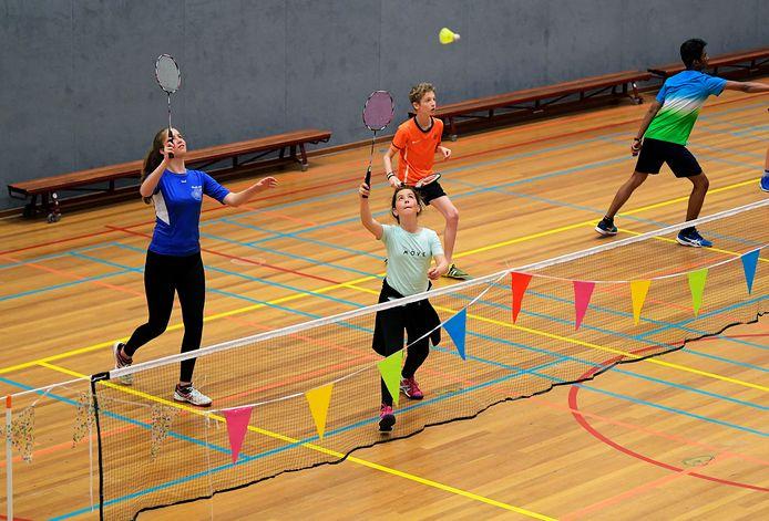 Feestelijke vlaggen aan het net bij Shuttle Up in Sliedrecht: de badmintonners kunnen eindelijk de training binnen weer oppakken.
