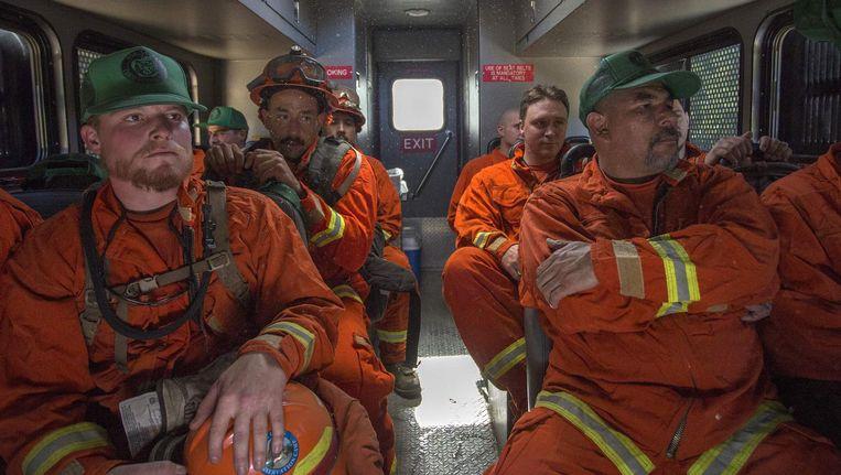 Gevangenen uit de gevangenis van Oak Glen op weg om te helpen bij het bestrijden van een bosbrand op 28 september eveneens in Californië Beeld AFP