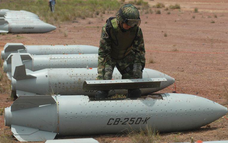 Een bomexpert van het Colombiaanse leger bekijkt een clusterbom, om hem onschadelijk te kunnen maken. © afp Beeld